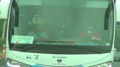 Photo of Captan a un conductor leyendo al volante de un autobús lleno de turistas.
